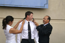 Nina and Dad putting shoulder insignias on Ensign Matt Paddock during commissioning ceremony
